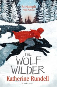 Book cover Text: 'A triumph' Philip Pullman The Wolf Wilder Katherine Rundell Bloomsbury Image: Illustration of a girl in a red coat riding a black wolf on a snowy landscape