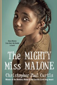 Text: Deza Malone from 'Bud, Not Buddy' is back! The Mighty Miss Malone Christopher Paul Curtis Winner of the Newbery Medal & the Coretta Scott King Award Image: Photograph of a girl looking upwards into the camera, a slight smile on her face