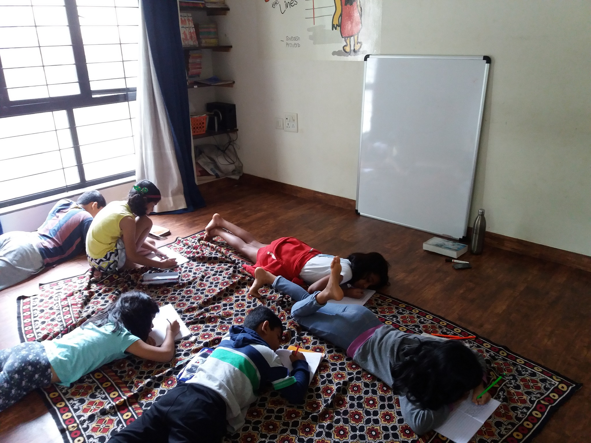 Children lying down and writing