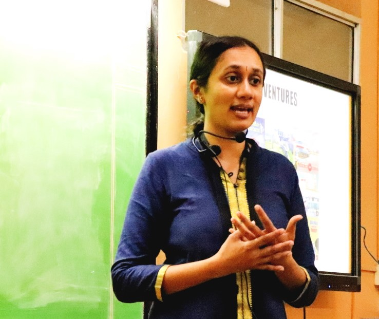 Varsha Seshan with collar mic in front of a screen displaying the railway adventures