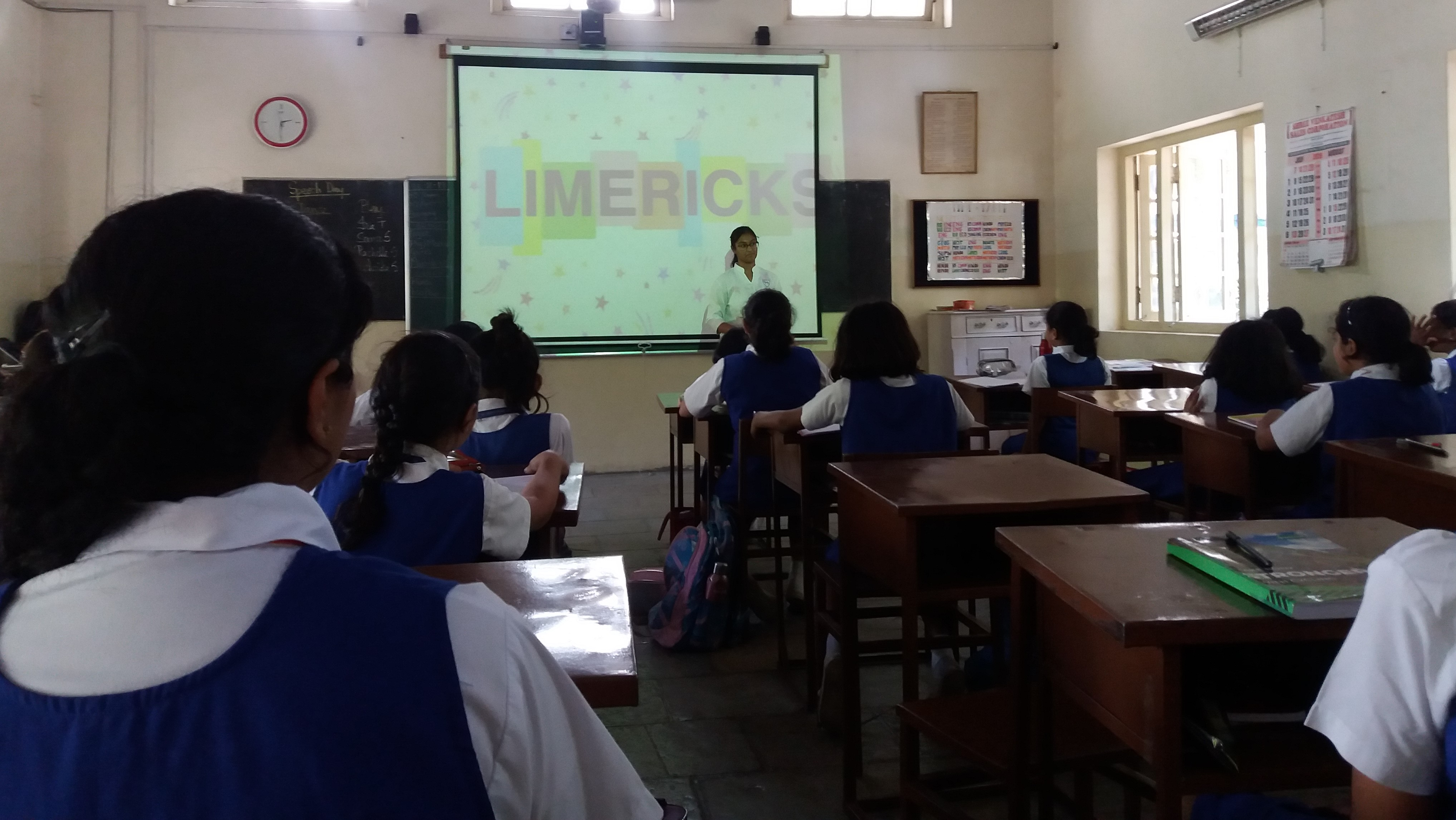 Audio-visual display that says 'Limericks' A student standing before it, talking to a class of girls (no faces visible)