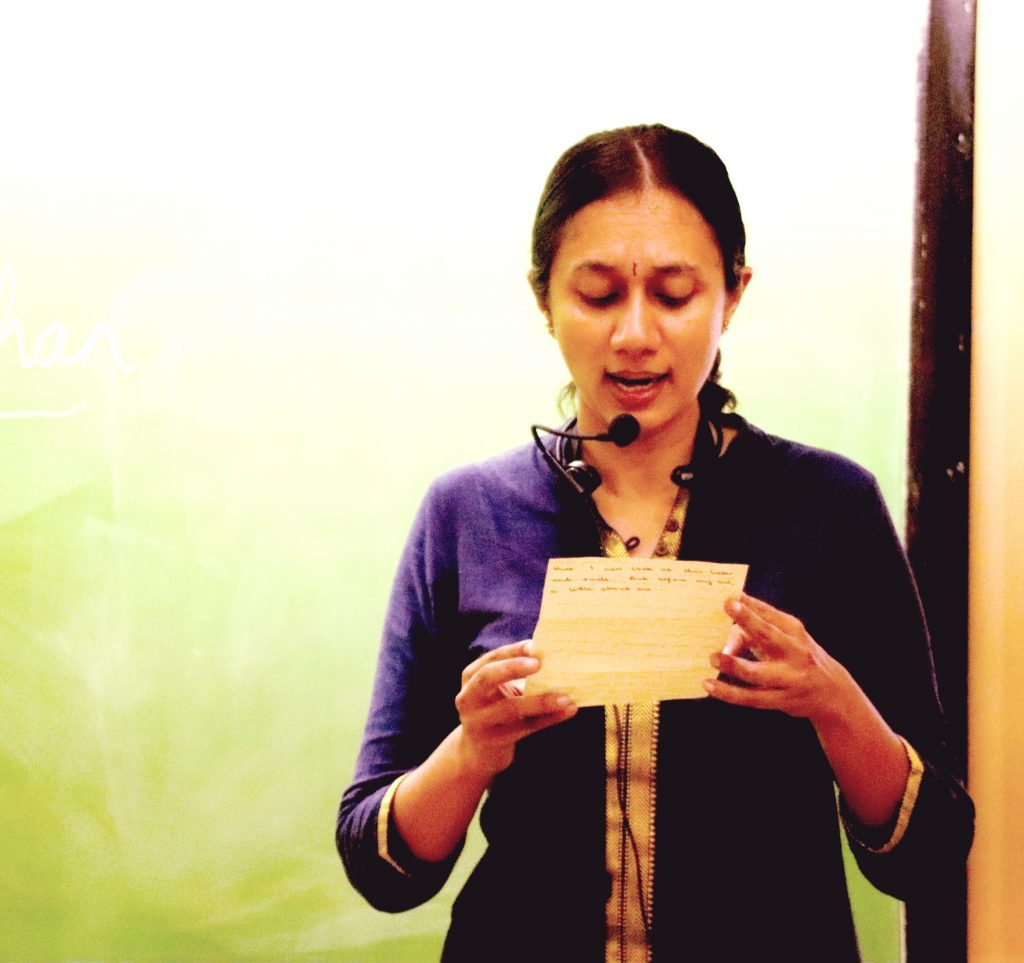 Varsha Seshan with a collar mic reading out a handwritten letter