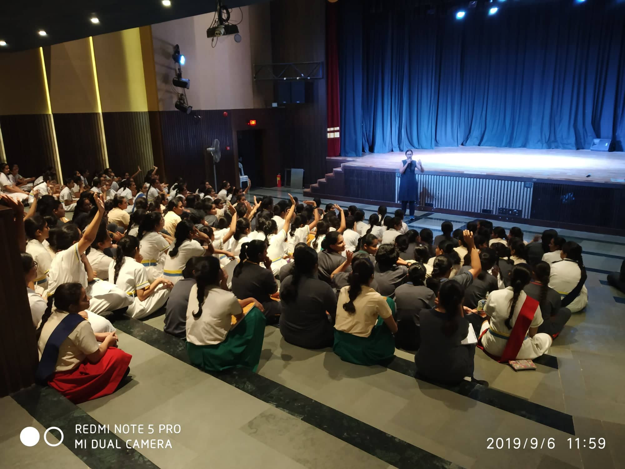 Varsha Seshan speaking on the mic to an audience of schoolgirls, many of who are raising their hands