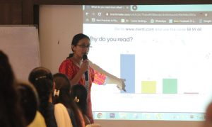 Varsha Seshan pointing to a bar graph which says 'Why do you read?'