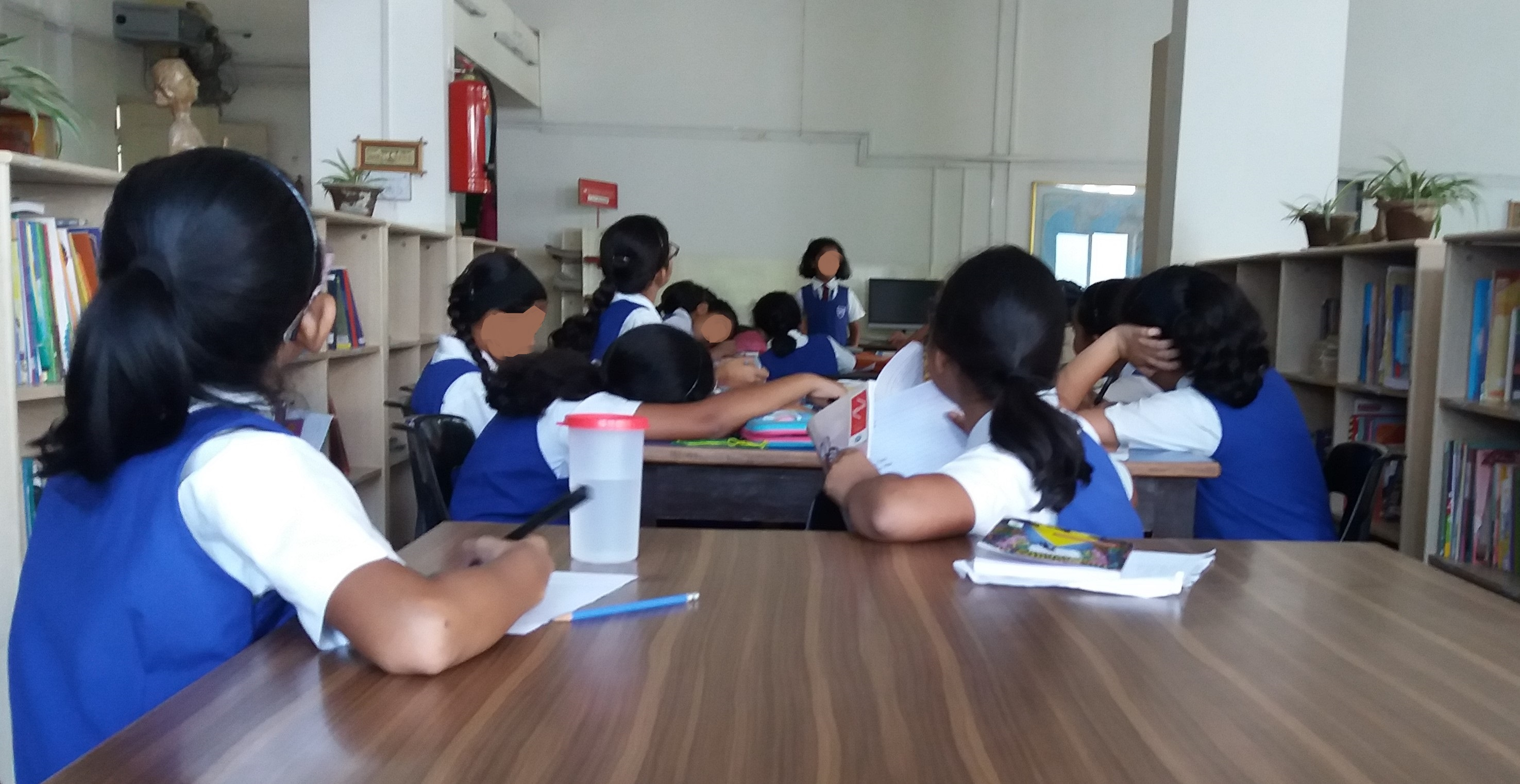 Girls sitting in a library looking ahead at one girl who is standing and speaking. Everyone is in uniform. Faces deliberately blurred.