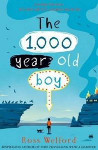 A boy and a cat in the middle distance (unclear), between a cliff with birds and another cliff with a burning house. Text - 'The 1,000 year old boy'