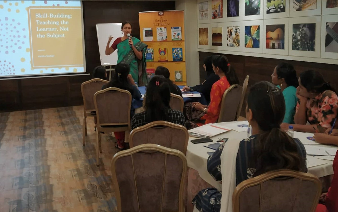 Varsha Seshan speaking on the mic to a group of teachers. In the background, a presentation that says 'Skill-Building: Teaching the Learner, Not the Subject'