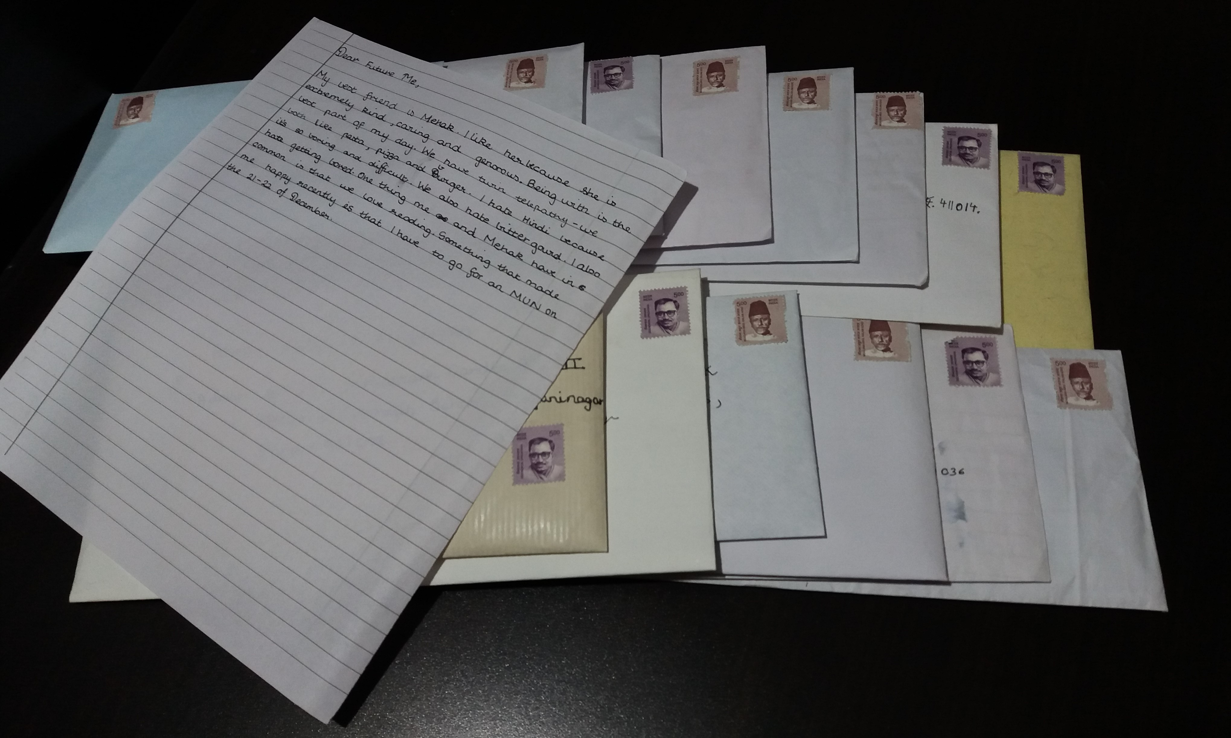Two piles of stamped envelopes, a handwritten letter on top to hide the addresses.