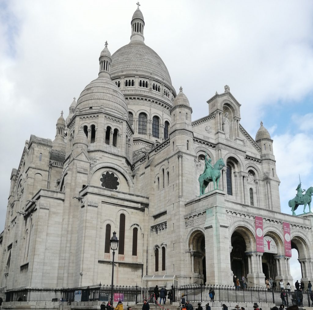 The Sacre Coeur - a white domed cathedral with two green statues of people horseback close to the entrance