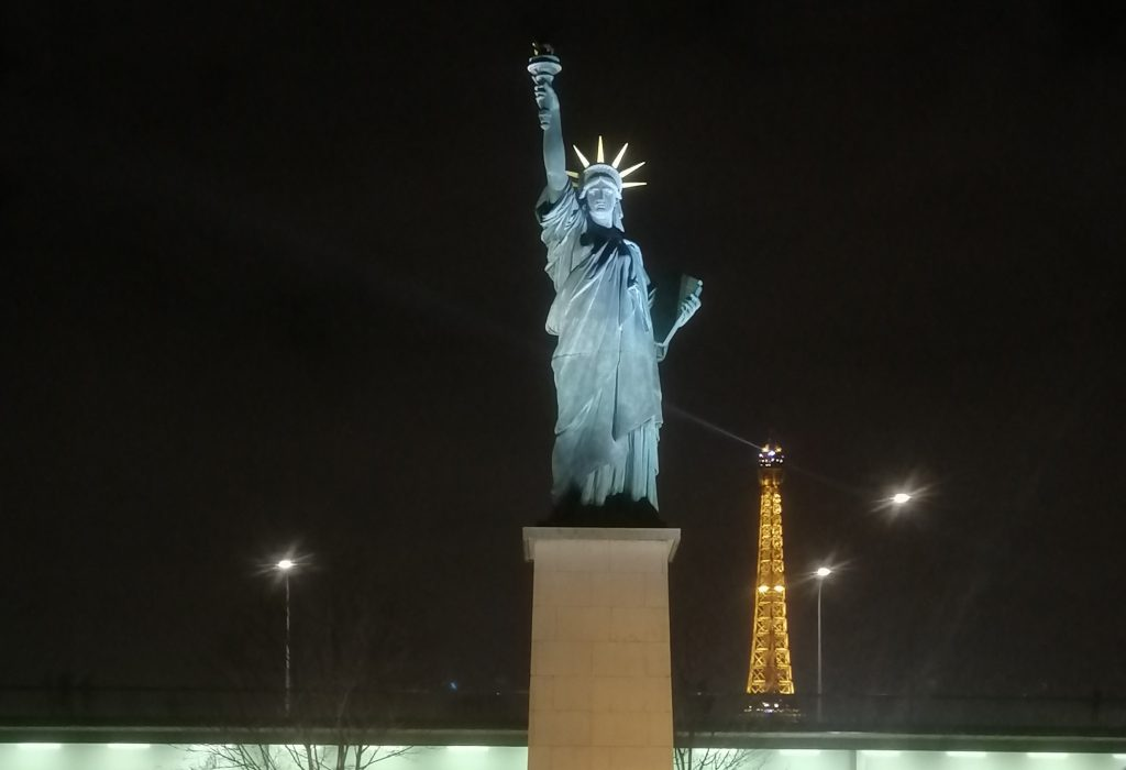 The Statue of Liberty with the Eiffel Tower in the background