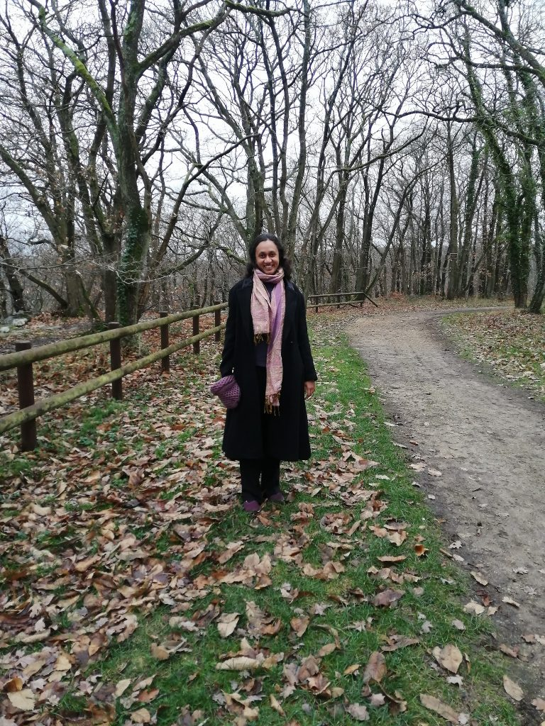 Varsha in the woods, treeless trees in the background, leaves on the grass
