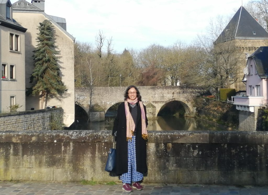 Varsha on a bridge, an arched bridge in the background