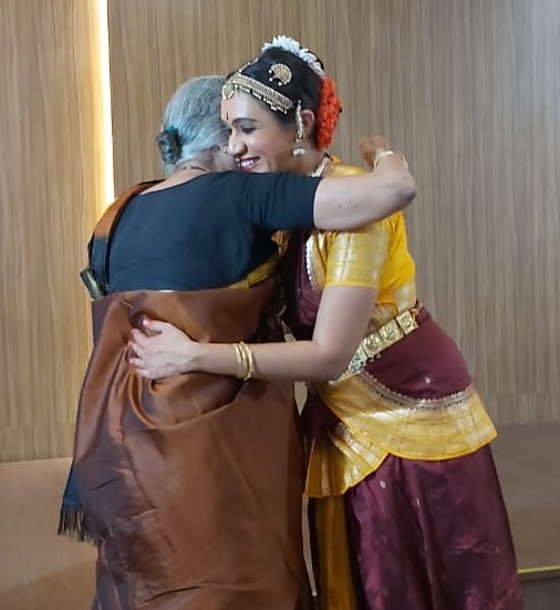 An older person hugging Varsha in dance costume