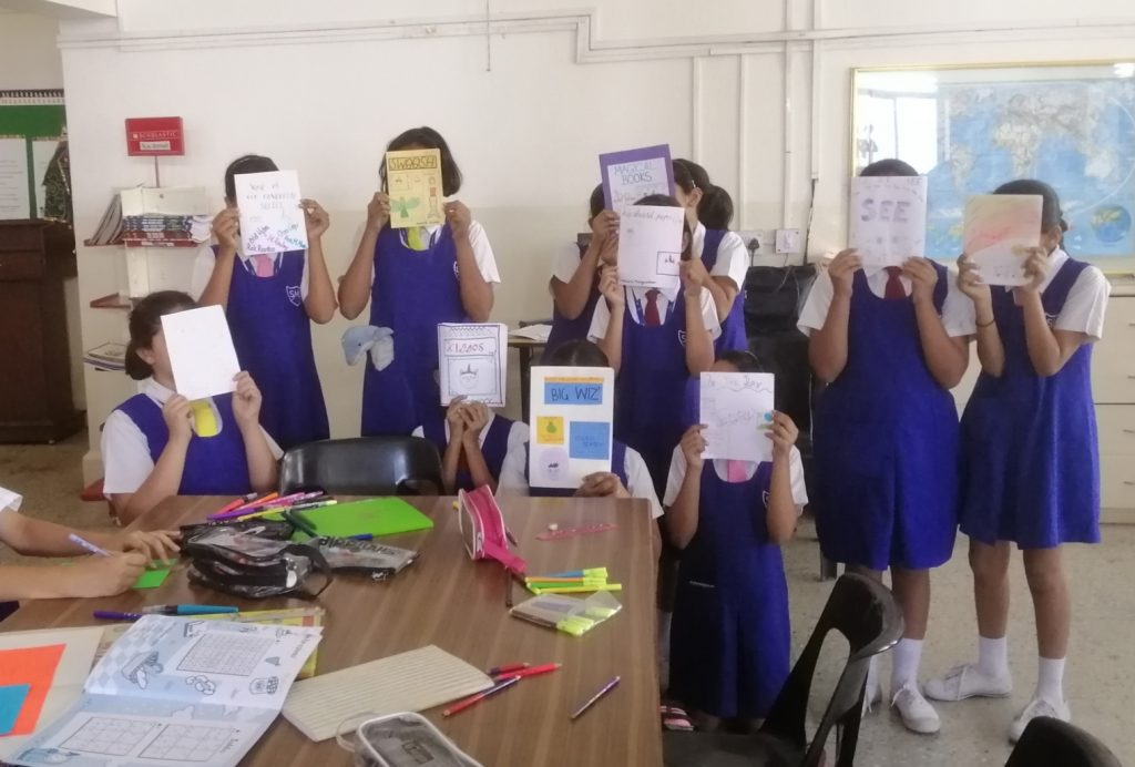 Ten girls in school uniform hiding their faces behind handmade magazines