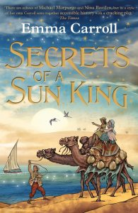 Book cover Text: 'There are echoes of Michael Morpurgo and Nina Bawden, but in a style of her own Carroll sews together accessible history with a cracking plot.' The Times Emma Carroll Secrets of a Sun King Image: Two girls sitting on a camel, a boy on the sand leading the other camel. Bacground of a boat, sparkling water and two birds invoking the idea of a desert.