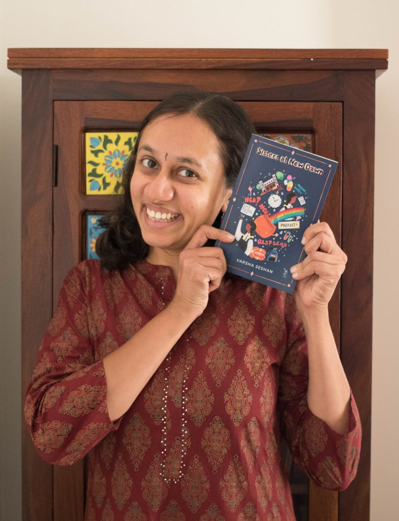 Varsha Seshan holding her book, Sisters at New Dawn