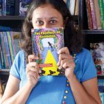 Varsha hiding half her face with the book The Prophecy of Rasphora