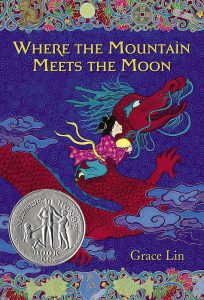 Book cover Text: Where the Mountain Meets the Moon Grace Lin Within a silver medallion, the text: Newbery Honor Book Image: A girl holding a pale yellow ball rides a red dragon in the clouds.