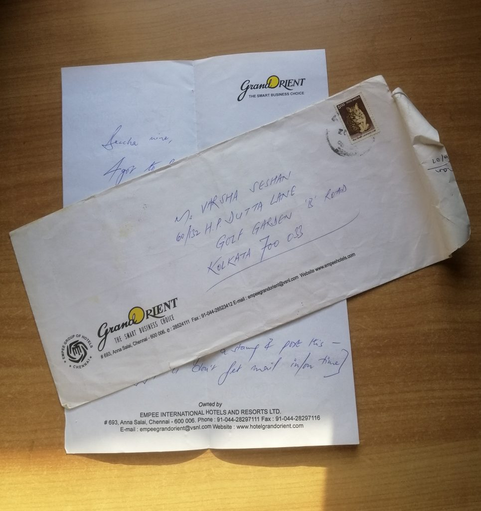 A letter covered partially by a stamped envelope. It's hotel stationery, visible as coming from Grand Orient.