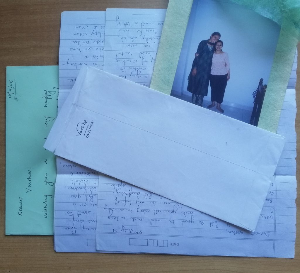 A pile of letters partially covered by a photograph of two girls and an envelop signed Varsha 06/07/05